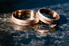 Anneaux de mariage pour des nouveaux mariés sur un fond foncé Photographie stock
