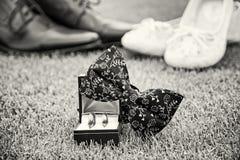 Anneaux de mariage, ` s de noeud papillon et de femmes et chaussures du ` s d'hommes, sans couleur Photographie stock libre de droits