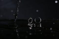 Anneaux de mariage sous des gouttes de l'eau Images libres de droits