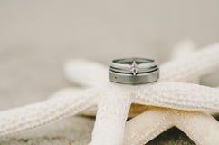 Anneaux de mariage sur des étoiles de mer Images stock