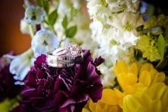 Anneaux de mariage sur des fleurs Photos libres de droits