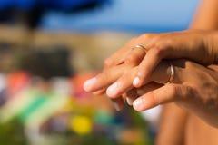 Anneaux de mariage sur des mains dans la lumière Images stock