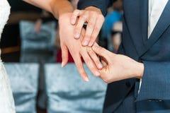 Anneaux de mariage sur des mains des nouveaux mari?s photographie stock libre de droits