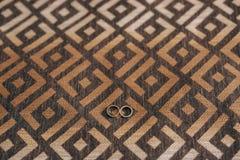 Anneaux de mariage sur l'ornement La texture des tissus pour le furnit photographie stock