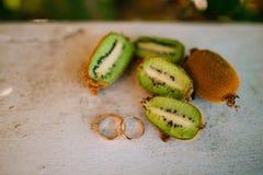 Anneaux de mariage sur la coupe du kiwi Photo stock