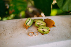 Anneaux de mariage sur la coupe du kiwi Image stock