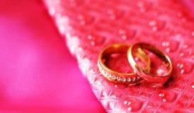 Anneaux de mariage sur la robe rose Amour et heureux Photo libre de droits