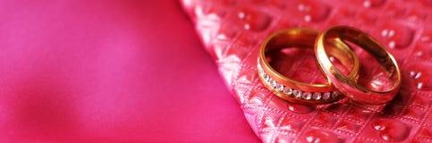 Anneaux de mariage sur la robe rose Amour et heureux Images libres de droits