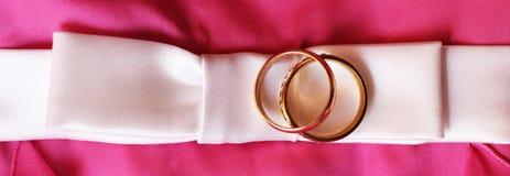 Anneaux de mariage sur la robe rose Amour et heureux Image libre de droits