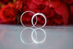 Anneaux de mariage sur le fond rouge de fleurs photographie stock libre de droits