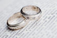 Anneaux de mariage sur le livre Image stock