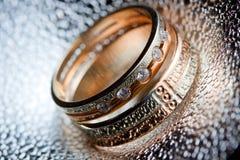 Anneaux de mariage sur le métal texturisé Photographie stock