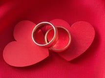 Anneaux de mariage sur les coeurs rouges Photographie stock