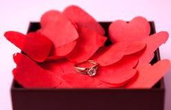Anneaux de mariage sur les coeurs rouges Fond rose Le concept des fiançailles, divorce, départ, infidélité Foyer sélectif images stock