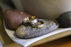 Anneaux de mariage sur pierres Photos stock