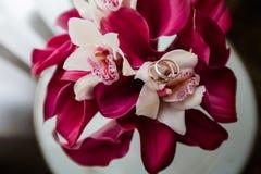 Anneaux de mariage sur un bouquet des fleurs photographie stock