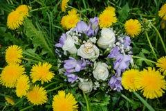 Anneaux de mariage sur un bouquet des roses en pissenlits Photos libres de droits