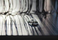 Anneaux de mariage sur un conseil en bois Photographie stock