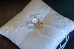Anneaux de mariage sur un coussin blanc avec l'espace de copie photos stock