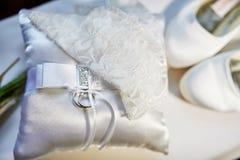 Anneaux de mariage sur un coussin, et les chaussures blanches de la jeune mariée photographie stock libre de droits