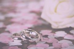 anneaux de mariage sur un fond en bois avec le vintage de confettis rétro Image libre de droits