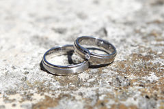 Anneaux de mariage sur un mur en pierre Photos libres de droits