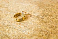 Anneaux de mariage sur une pierre naturelle avec des inclusions d'or indigène Mains et coeurs d'offre Images libres de droits