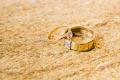 Anneaux de mariage sur une pierre naturelle avec des inclusions d'or indigène Mains et coeurs d'offre Photos libres de droits
