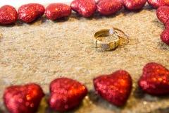 Anneaux de mariage sur une pierre naturelle avec des inclusions d'or indigène Mains et coeurs d'offre Photo stock