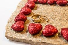 Anneaux de mariage sur une pierre naturelle avec des inclusions d'or indigène Mains et coeurs d'offre Image stock
