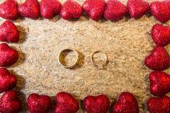 Anneaux de mariage sur une pierre naturelle avec des inclusions d'or indigène Mains et coeurs d'offre Photographie stock libre de droits