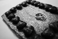 Anneaux de mariage sur une pierre naturelle avec des inclusions d'or indigène Mains et coeurs d'offre Image libre de droits