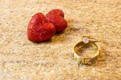 Anneaux de mariage sur une pierre naturelle avec des inclusions d'or indigène Mains et coeurs d'offre Photographie stock