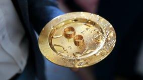 Anneaux de mariage sur une soucoupe dans l'église Cérémonie de mariage Anneaux des jeunes mariés banque de vidéos