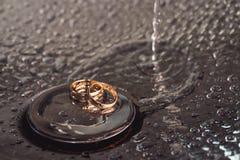 Anneaux de mariage sur une surface plaquée par chrome baisses de l'eau avec des réflexions de lumière le fond 3d rendent éclabous Images stock