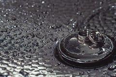 Anneaux de mariage sur une surface plaquée par chrome baisses de l'eau avec des réflexions de lumière le fond 3d rendent éclabous Image stock