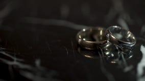 Anneaux de mariage sur une table en pierre de marbre noire Deux anneaux sur une table de marbre noire Images libres de droits