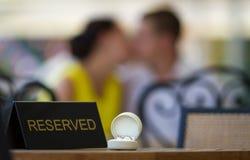 Anneaux de mariage sur une table et un couple de baisers Images libres de droits