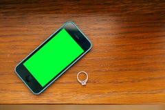 Anneaux de mariage sur une texture en bois, un smartphone bleu et noir W Images libres de droits