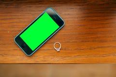 Anneaux de mariage sur une texture en bois, un smartphone bleu et noir W Photographie stock