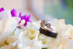 Anneaux et fleurs de mariage Image stock