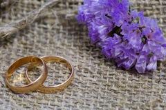 Anneaux et fleurs de mariage sur un fond de toile image libre de droits