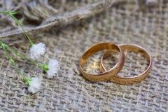 Anneaux et fleurs de mariage sur un fond de toile photographie stock