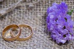 Anneaux et fleurs de mariage sur un fond de toile image stock