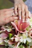 Anneaux et mains de mariage au bouquet de mariage Image stock