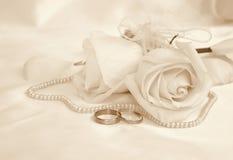 Anneaux et roses de mariage comme fond de mariage Dans la sépia modifiée la tonalité r Photographie stock