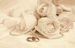 Anneaux et roses de mariage comme fond de mariage Dans la sépia modifiée la tonalité r Image libre de droits