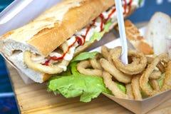 Anneaux frits de calmar montrés sur le petit pain de pain et le cardbox Images libres de droits
