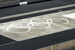 Anneaux olympiques dans la terre photographie stock libre de droits