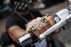 Anneaux sur des doigts tenant la moto image stock